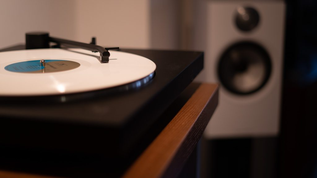 Turntables in warm light with a blurred speaker and white disk