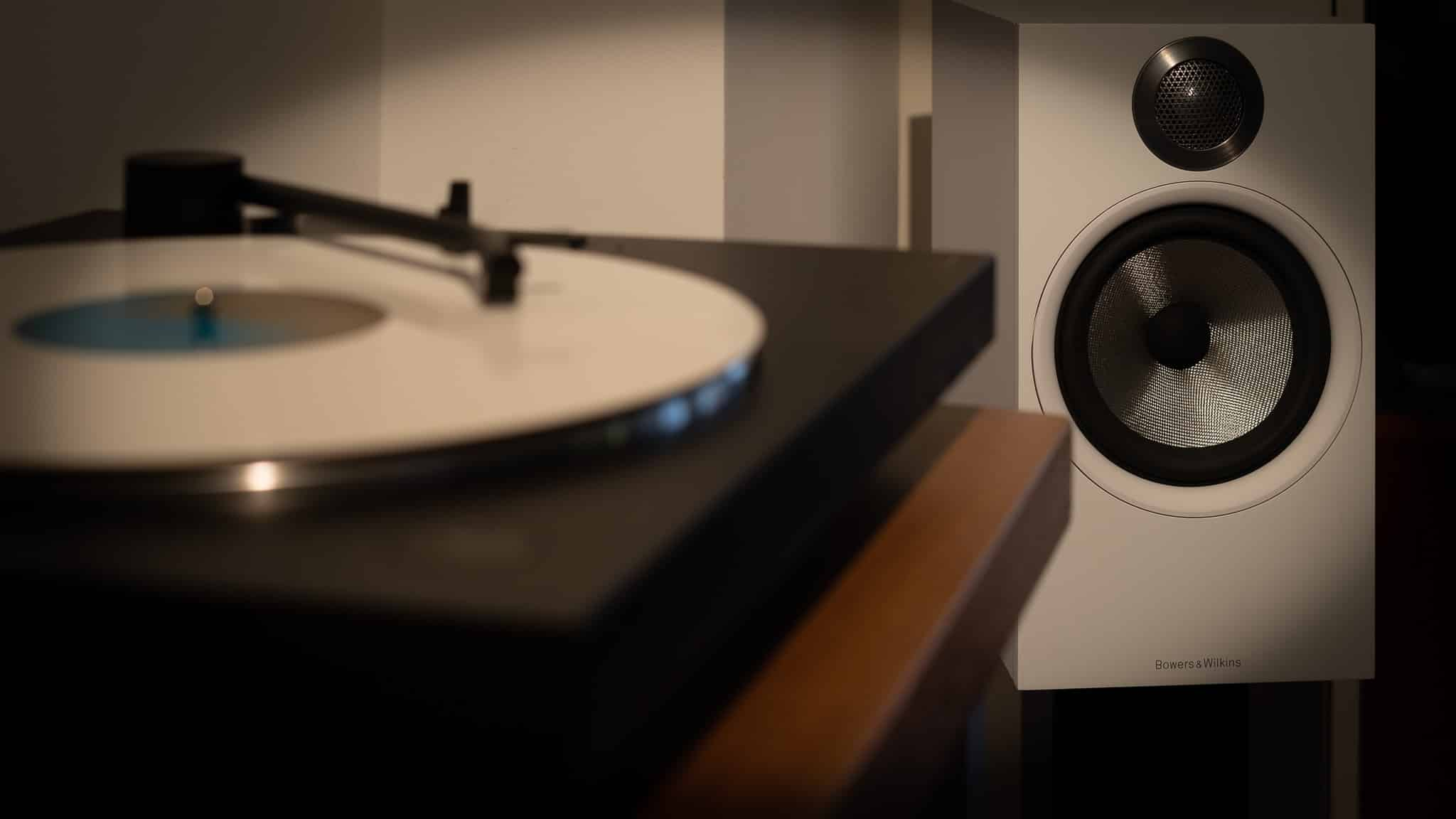 Blurred turntables in warm light with in focus speaker and white disk